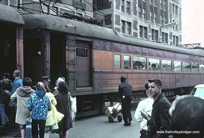CSS&SB Train 320 boarding passengers in street at South Bend, Indiana station on April 9, 1966. Rick Burn and Steve Summer at right