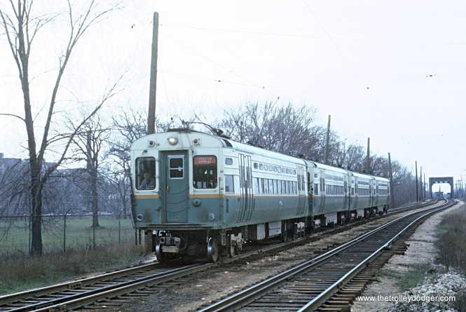 CTA 4-car Evanston Express approaching Isabella Ave. station with 4 trolley poles up, Evanston, IL, North Shore Channel bridge in background on April 12, 1966 These are single man cars used individually as shuttles on the Evanston Line during off hours.