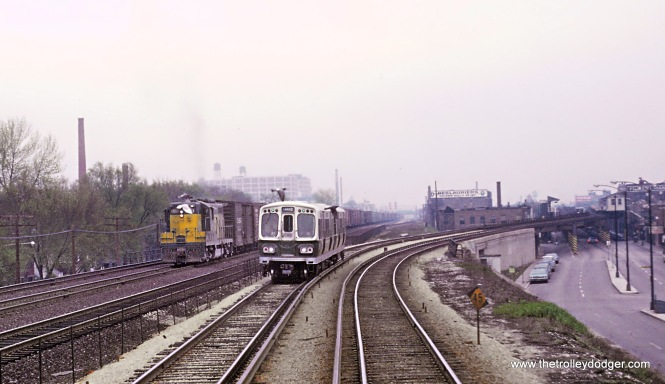 "1 of 2 Photos. On the slide mount Roger wrote, ""CTA Lake St. B-train racing C&NW freight near Laramie Ave., Chicago, IL in May 1967."" Before October 28, 1962 the Lake St. ""L"" ran at street level next to the C&NW's elevated embankment through far western Chicago and Oak Park after it dismounted its ""L"" structure above Lake Street. It was slow running with lots of grade crossings. On that date the trains shifted to new tracks up on the embankment. Roger's photo shows the results. At the right you can see the structure over Lake Street and see the tracks shift to the left (north) on to the C&NW embankment. And I really like this photo. Why? It's the pigeons. Four of them."