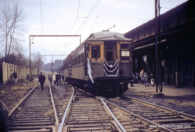"A two-car train of CTA woods makes a fantrip stop in the 1950s at the ground-level Buena Yard, which was an interchange point for freight between the ""L"" and the Milwaukee Road up until 1973. Under the ""L"", you can see remnants of the former Buena station, which closed in 1949. In the distance, there is a ramp leading up to the ""L"". This site is now the location of Challenger Park. (John Smatlak Collection)"