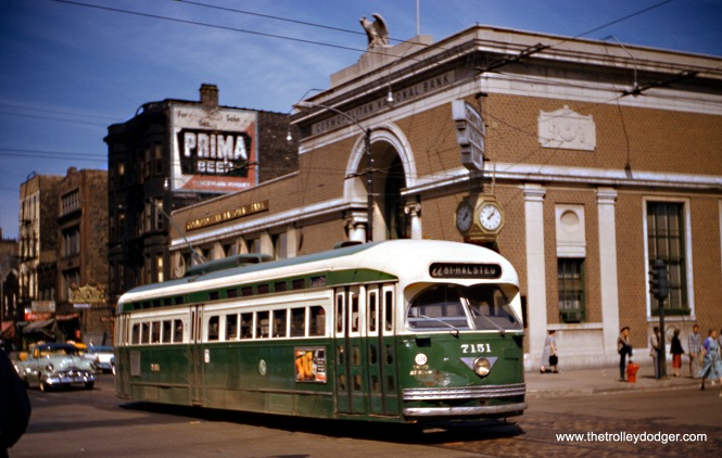 CTA 7151 is southbound at Clark Street and Chicago Avenue, passing by what is now the former Cosmopolitan Bank Building, designed by the firm of Schmidt, Garden & Martin and built in 1920. The northern portion of the building was a 1930 addition, and was redone in 1995, in a style matching the original portion. (Robert Heinlein Photo)