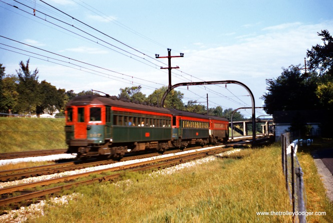 A North Shore Line train on the Shore Line Route is southbound in Winnetka in September 1954. This section was grade-separated in 1940, along with the adjacent Chicago & North Western tracks, following a series of pedestrian accidents. Harold L. Ickes, Secretary of the Interior under President Franklin D. Roosevelt, approved Federal aid that paid for part of this work, in a similar fashion to Chicago's Initial System of Subways. Ickes had lived in the area for many years. The train is moving towards the photographer, and the front is blurred due to the shutter speed that had to be used, in the days when Kodachrome was ISO 10. (Wien-Criss Archive)