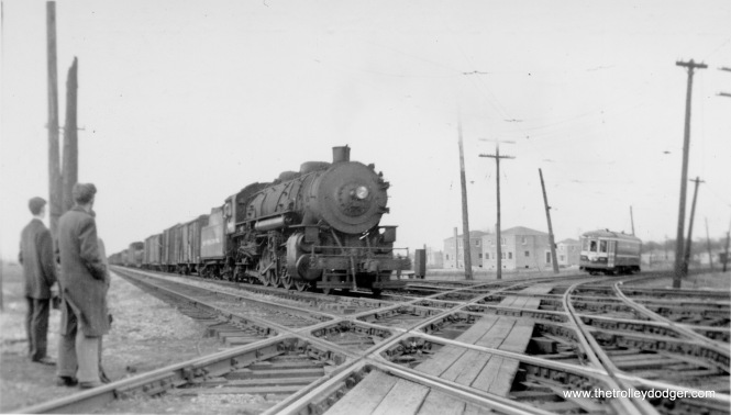 "A ""meet"" between a steam train and a Chicago & West Towns Railway streetcar in LaGrange in the late 1940s. You can see evidence of the postwar construction boom in the background. Not sure if this was a fantrip."