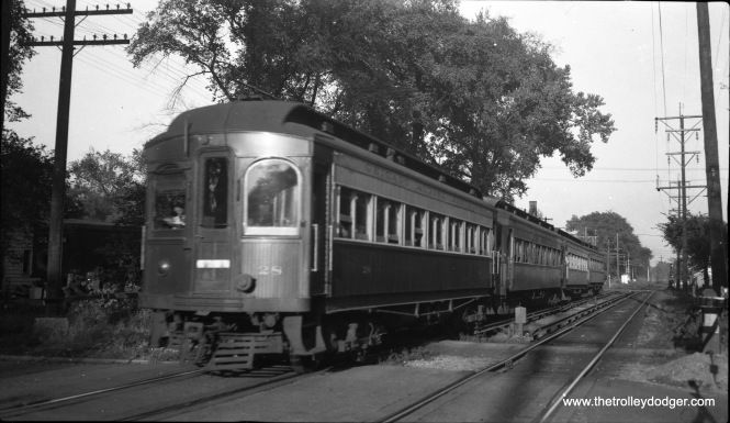 Chicago Aurora & Elgin wood car 28 in Forest Park in 1952. The front of the car is not in sharp focus because it was moving towards the photographer. Back then, film speeds, and therefore shutter speeds, were quite slow. The fastest film speed in use then was Kodak Super-XX, introduced in 1940, at ISO 200. But this is probably not that film. Panatomic-X, which Kodak began selling in 1933, was ISO 32, and Plus-X, introduced in 1938, was originally ISO 50 (later bumped up to 125). Photographers often dealt with the shutter speed problem by taking their pictures while a train was still at a distance. The tracks curve off to the right in the distance. I am not sure of the exact location, although the Eisenhower expressway is here now.