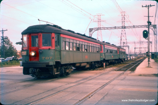 NSL 707 heads up a northbound train crossing Dempster Street in Skokie in September 1958. Just behind the train, you can see a tiny bit of the station, which has been preserved and moved to a slightly different location. The southbound shelter was much more basic, and was approximately where the CTA built a new platform for Skokie Swift trains in 1964. Again, this was an early Ektachrome slide that had shifted to red (actually, it was the other color dyes that badly faded, leaving mostly the red visible) and was restored in Photoshop. (J. William Vigrass Photo)