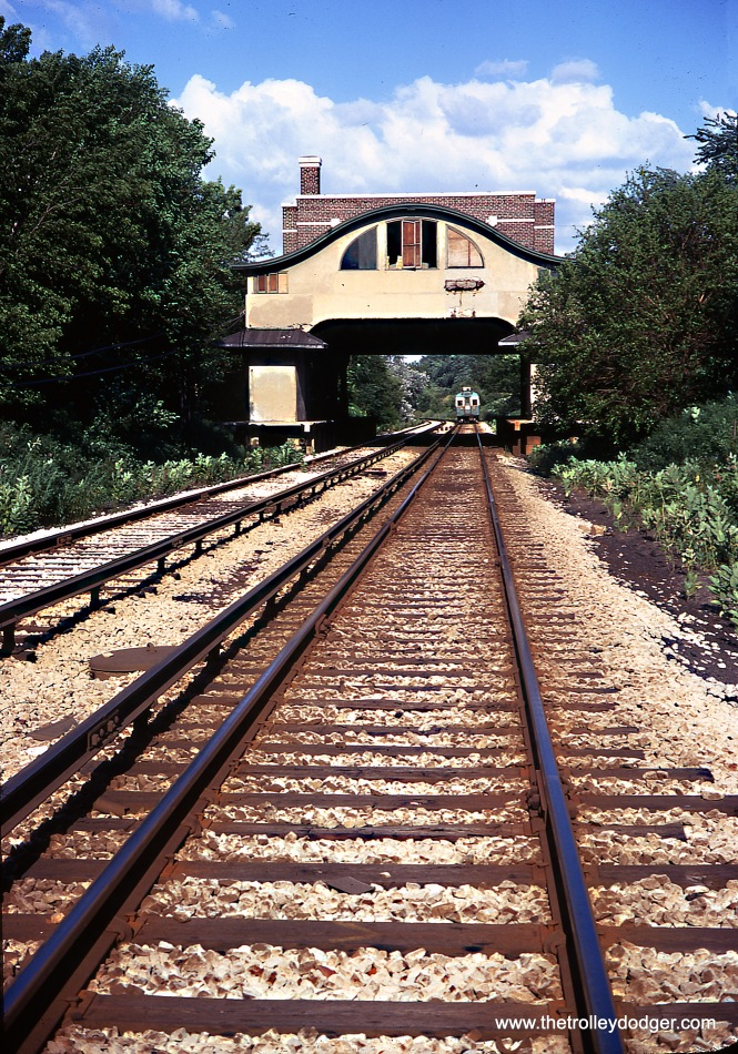 "The former Asbury station on the Niles Center ""L"" branch (unused by transit since 1948), as it looked in July 1970. The picture was taken along the right of way of the CTA Skokie Swift (today's Yellow Line). The building has long since been demolished. A train in the 5001-5004 series is visible in the distance."