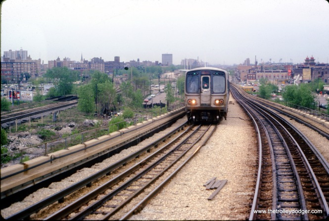 I thought this was interesting as it is an unusual view, one that you could only get by taking a picture on a moving train. This is near the Cermak station on the CTA Dan Ryan Line on May 14, 1979. A northbound train of 2000s approaches, and old Comiskey Park is visible to the south.