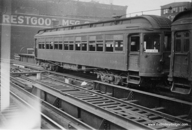 "The North Shore Line began running into Chicago via the ""L"" in 1919, and had phased out use of wood cars by 1936. This shows car 130 at Roosevelt Road in that time frame, signed for the Shore Line Route. During WWII, NSL leased this and some other wood cars to the Chicago Aurora & Elgin. A train of woods ran a fantrip on the North Shore Line in 1946, and then these cars were sold to the CA&E, which continued to operate them until service was cut back to Forest Park in 1954. The glare may indicate this picture was taken looking through the window of another train."