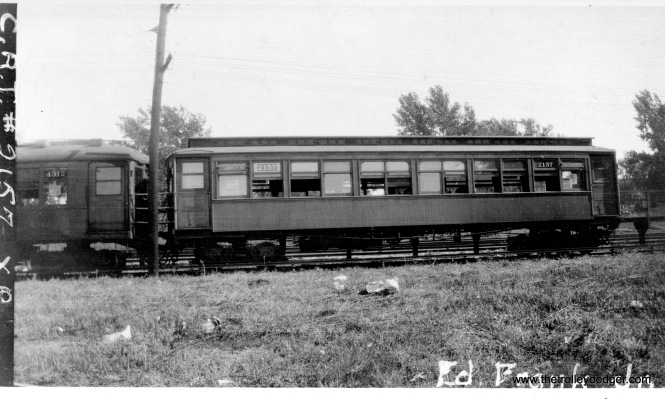 "I find this photo by Edward Frank, Jr. interesting for a number of reasons. It most likely is from before 1943, as a CRT steel car (4312) is coupled to a wood car (2157). This is along the Garfield Park line and the notation ""XO"" on the side probably means this train is turning back just west of the DesPlaines Avenue station in Forest Park (which would also explain why there is a cemetery visible behind the train). The platform that's visible may have been only for the use of train crews. The Eisenhower Expressway is located here now. It is unusual that Ed Frank put his name directly on the negative-- he generally rubber stamped it on the back. He was taking pictures as early as 1934."